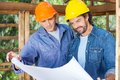 Architects studying blueprint at site male together in wooden cabin Stock Photos