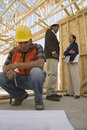 Architects talking and worker looking at blueprints two with construction in foreground Royalty Free Stock Image