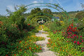 Archway flowers photo of with home of claude monet in the background at giverny france these gardens inspired many of claude Stock Image