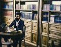 Aristocratic lifestyle concept. Man in classic suit sits in vintage interior, library Royalty Free Stock Photo