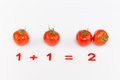 Arithmetic example of tomatoes and red numbers on the addition of a white background Royalty Free Stock Image