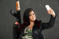 Armed girl taking selfie attractive holding an automatic rifle in one hand and in the other hand a mobile phone with which Stock Image