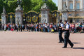Armed police patrol in front of the buckingham palace while a daily guard changing may london uk Royalty Free Stock Photos