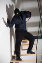 Armed robber on stairs Stock Photo