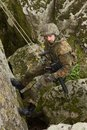 Armed soldier hanging on a cliff Royalty Free Stock Photo