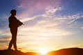 Armed soldier with rifle guard army military war standing and looking on horizon silhouette at sunset Royalty Free Stock Image