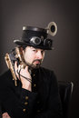 Armed steam punk man in steampunk outfit holding a gun in his hand and a hat on his head Stock Images