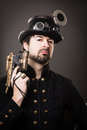 Armed steam punk man in steampunk outfit holding a gun in his hand and a hat on his head Royalty Free Stock Image