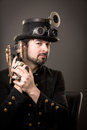 Armed steam punk man in steampunk outfit holding a gun in his hand and a hat on his head Stock Photo