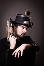 Armed steam punk man in steampunk outfit holding a gun in his hand and a hat on his head Royalty Free Stock Photography