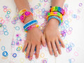 Arms of a child wearing multicoloured bracelets colourful elastic loom band worn on hands against white table top Royalty Free Stock Photos