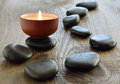 Aroma candle with spa stones on a wooden background selective focus Royalty Free Stock Images