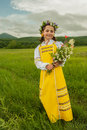 Aroma of summer in an elegant russian sundress girl enjoys wild flowers Royalty Free Stock Photography