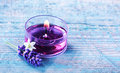 Aromatherapy spa background with a sprig of fragrant lavender alongside a burning candle with essential oil and plant extracts in Stock Photo