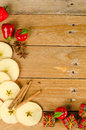 Aromatic apples on a wooden table sliced in still life with cinnamon sticks and christmas decoration Stock Photos