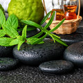 Aromatic spa still life of bottles essential oil, fresh mint, rosemary, bergamot fruits, towels and candles on zen stones Royalty Free Stock Photo