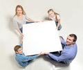 Around the white square four people father son mother and daughter sitting on a floor are holding a Stock Images