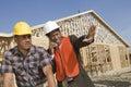 Arquitecto on call gesturing hacia sitio con el compañero de trabajo Imagenes de archivo