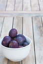 Arrangement of damson plums on wooden boards fresh whole ripe purple in a bowl and just harvested from the garden and a healthy Stock Photos