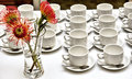 Array of empty tea/coffee cups and flower vase on white table Royalty Free Stock Photo