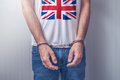 Arrested man with cuffed hands wearing shirt with UK flag Royalty Free Stock Photo