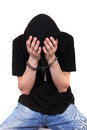Arrested young man in handcuffs hide his face isolated on the white background Royalty Free Stock Image