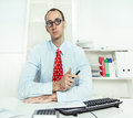 Arrogant man sitting at desk with glasses a red tie and a blue shirt working an insurance or bank know it all Royalty Free Stock Photo
