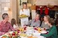 Arrosto del tacchino della tenuta della donna con la famiglia al tavolo da pranzo Immagini Stock