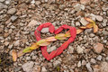 An arrow through the heart with leaves made ​​of on sand in background Stock Photography