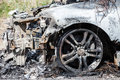 Arson fire burnt wheel car vehicle junk road wreck accident or Stock Photography