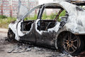 Arson fire burnt wheel car vehicle junk road wreck accident or Stock Images