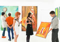 Art collectors at exhibition opening man holding and showing a colorful painting to other people in an gallery Stock Photo
