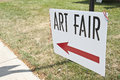 Art fair a sign that says with a red arrow pointing left Stock Photos