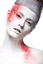 Art fashion girl with white skin and red paint on