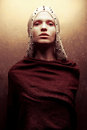 Art-fashion portrait of glamorous queen-warrior in golden cape Royalty Free Stock Photo