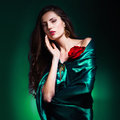 Art portrait of a beautiful woman in green dress whith rose Royalty Free Stock Images