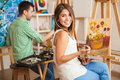 Art workshop for adults beautiful young hispanic women and a handsome men attending a painting together and having fun Royalty Free Stock Photography