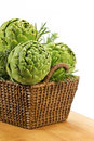 Artichokes in basket three globe with fresh herbs wicker on white background Royalty Free Stock Image