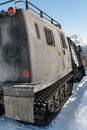 Articulated military tracked cargo vehicle on snow rear view Royalty Free Stock Image