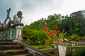 An artificial bridge with four statues of dragons with twisted tails, Tirta Gangga park, Karangasem, Bali, Indonesia Royalty Free Stock Photo