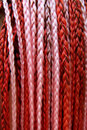 Artificial colorful braided hair red and pink Royalty Free Stock Photos