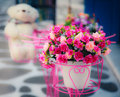 Artificial flower in vase with blurry doll in the background vintage look Stock Photo