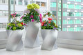 Artificial flowers in vases assorted arranged elegant placed near the window Stock Photography