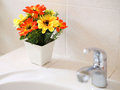 Artificial flowers at wash basin in a bathroom Royalty Free Stock Image