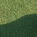 Artificial grass fake turf synthetic lawn field macro closeup with gentle shaded shadow area, green sports texture background Royalty Free Stock Photo