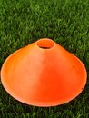 Artificial green plastic grass in background with  bright orange plastic cone. Mark on winter footbal playground. Royalty Free Stock Photo