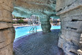 Artificial rock swimming pool view of a from under a pathway made of behind a waterfall Royalty Free Stock Photography