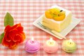 Artificial rose and fruit cake and candles Royalty Free Stock Photo