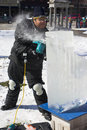 An artist carving a block of ice Royalty Free Stock Images
