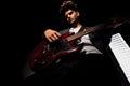 Artist in dark backgroud playing guitar Royalty Free Stock Photo